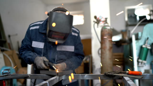 Welding in workshop Senior man welding metal in workshop iron metal stock videos & royalty-free footage