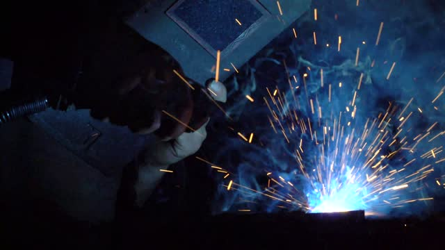 welding iron pieces while creating blue sparks