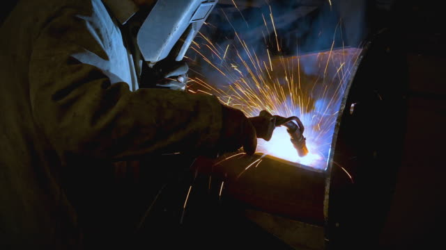 welding process on old metalworking factory, welder in mask working with sparks and smoke