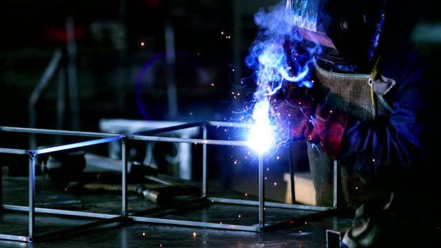 Welding process. Closeup side view of unrecognizable worker welding two metal plates with gas welding machine.He's wearing welding mask and protective workwear and gloves. 4k production line worker stock videos & royalty-free footage