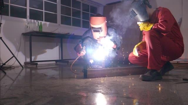 Welding Worker Slow Motion shot of Steel welder welding pipe in a metal workshop, Bangkok Thailand metal worker stock videos & royalty-free footage