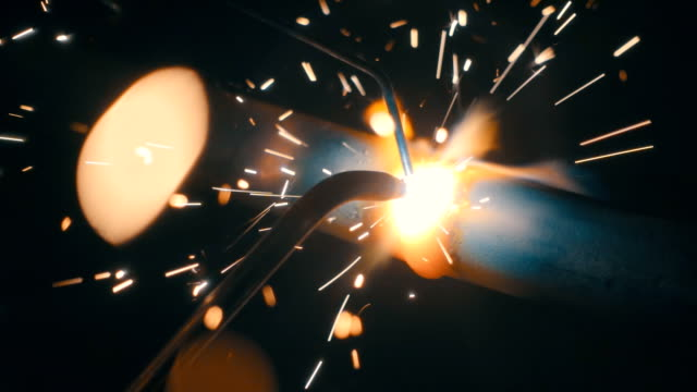 welding works on a black background and a lot of sparks flying around. slow mo, slo mo - saldare video stock e b–roll