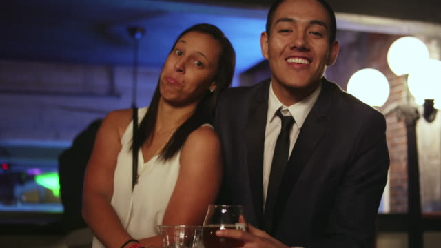 Well dressed man and woman posing for an awkward picture together at a nightclub video