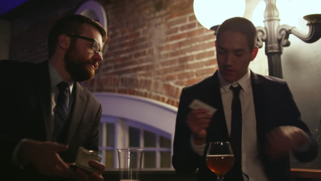 a well dressed young man hands his business card to another man at a nightclub - business card stock videos & royalty-free footage