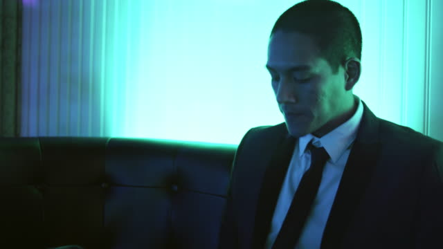 Well dressed young man on a couch in a nightclub takes a drink and looks at his phone video