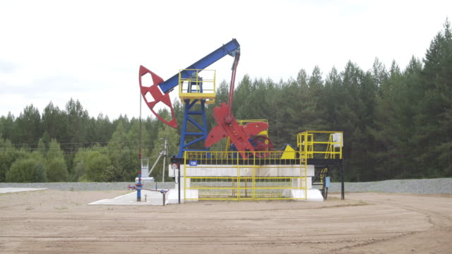 well pump jack operating. drilling rig extract crude oil. oil mining machine pumping crude oil for fossil fuel energy in oil field. cross type christmass tree destined for wellhead sealing. - opec video stock e b–roll