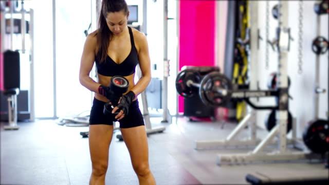 well trained fit woman workout triceps lifting weights in gym - biustonosz sportowy filmów i materiałów b-roll