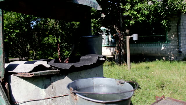 Well with water, there is iron bucket next to it. Extraction of water in rural areas. Life without running water video