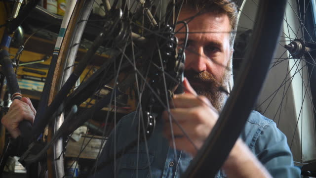 well-groomed handsome bearded master hipster, specialist in bicycles, repairing a bicycle in his workshop, wheels, frame, spokes, the background of tools. - warsztat filmów i materiałów b-roll