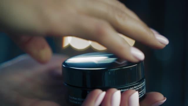 vídeos de stock, filmes e b-roll de mãos de mulher aprumado abrir um produto de beleza e mostra-lo para a câmera. feminino aberto suavemente metálico pote de creme. closeup, mo lento - maquiagem e cosméticos