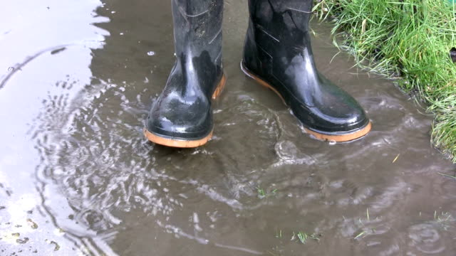 Wellington boots splashing in a muddy puddle Wellington boots splashing in a muddy puddle on the garden path. stamping feet stock videos & royalty-free footage