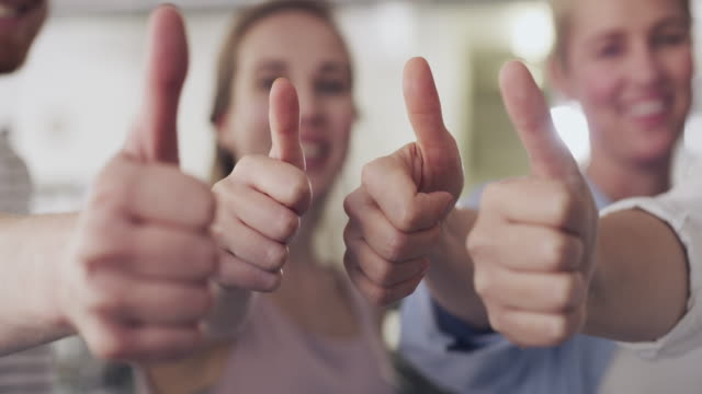 We're super proud of you! 4k video footage of a group of businesspeople showing thumbs up in a modern office representing stock videos & royalty-free footage