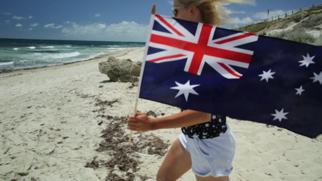 Western Australia Running flag close up of woman running on white beach waving Australian Flag. Blonde tourist enjoying in Mettams Pool, North Beach near Perth in Western Australia. Sunny day, Blue sky. Beach freedom summer holiday natal stock videos & royalty-free footage