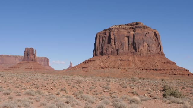 western buttes of red orange sandstone rock formations in monument valley usa - hochplateau stock-videos und b-roll-filmmaterial