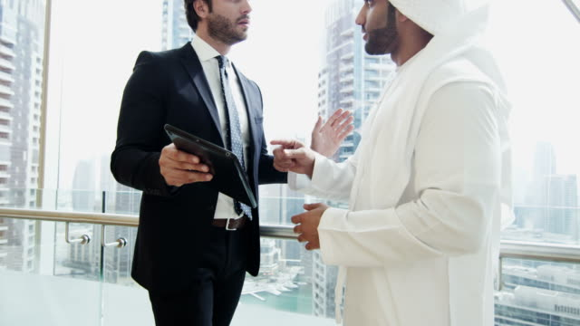 Western Caucasian Arabic male businessmen meeting using tablet video