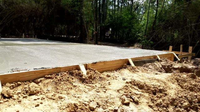 Wet concrete freshly poured in preparation for construction foundation. video