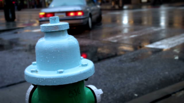 Wet Fire Hydrant covered in raindrops in busy metropolitan downtown city area video
