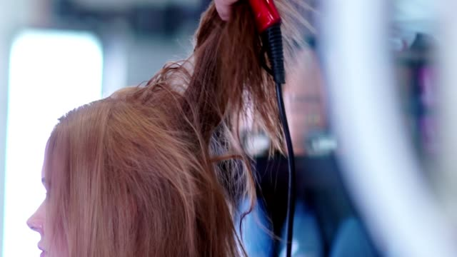 Wet hair is dried by hairdryer. Male hand stylist with a hairdryer video