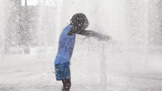 Wet little girl running and having fun in the jet fountain at city public park.