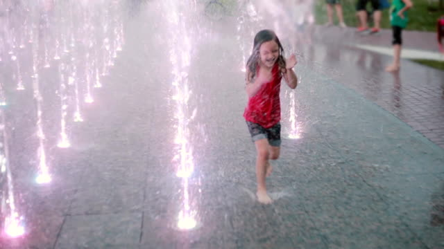 wet little girl running through the water jets at the fountain and laughing. child having fun in hot summer day - fontana struttura costruita dall'uomo video stock e b–roll