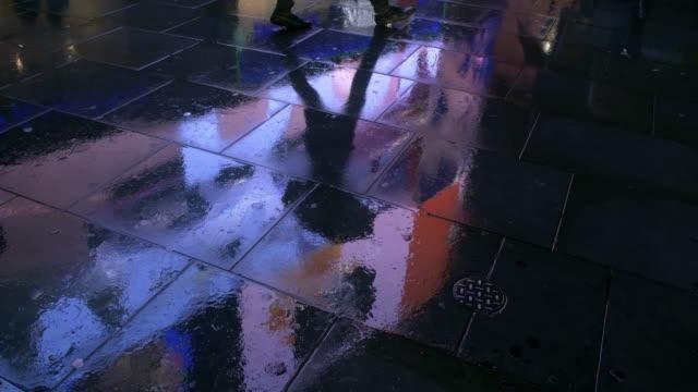 vídeos de stock e filmes b-roll de wet pavement reflecting city lights - poça