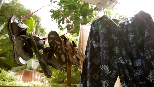 Wet sandals and shorts drying on the balcony. Clothes and shoes hanging on a hanger. Phuket, Thailand video