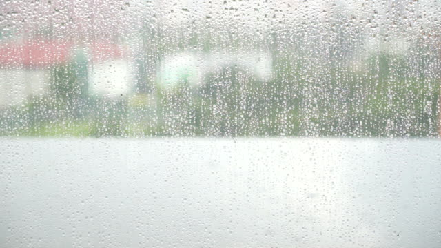 Wet window glass, Rain drops on window glass surface with cloudy blurred city background video
