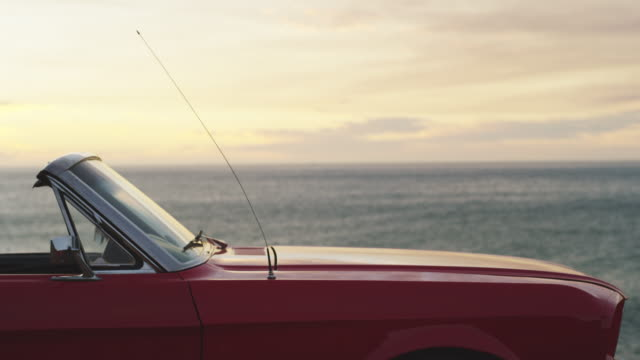 What a beautiful place to stop 4k video footage of a convertible parked at the beach overlooking the ocean stationary stock videos & royalty-free footage