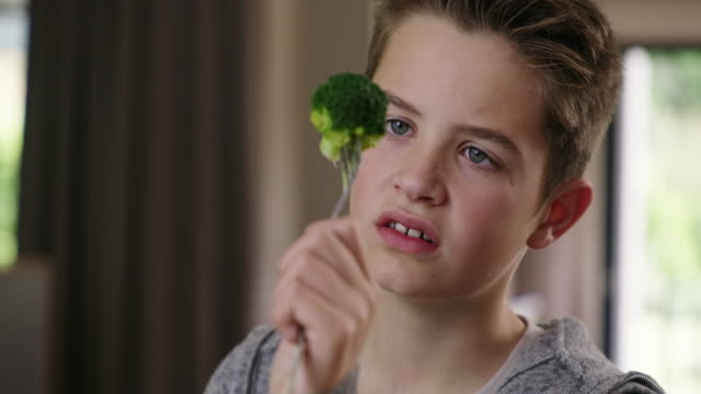 What is it? Some kind of alien? 4k video footage of a young boy refusing to eat his broccoli at home tasting stock videos & royalty-free footage