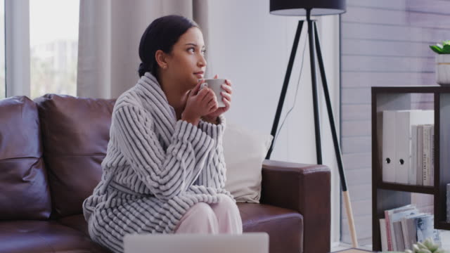 What is the rest of the world doing right now? 4k video footage of a beautiful young woman enjoying a coffee break on the sofa at home laziness stock videos & royalty-free footage