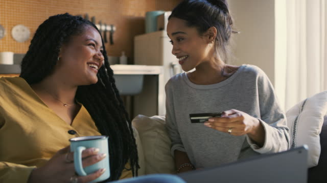 What should we buy? 4k video footage of two cheerful young women doing online shopping together on a laptop while being seated on a couch at home electronic banking stock videos & royalty-free footage