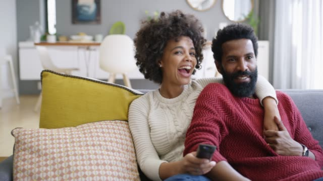 What will you be watching this weekend? 4k video footage of a young couple watching tv on the sofa at home watching tv stock videos & royalty-free footage