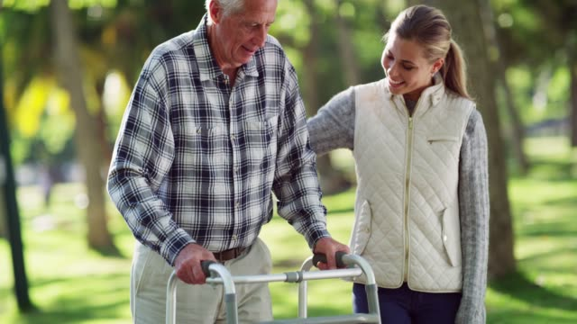 What you do for them will never be forgotten 4k footage of a senior man using a walker while out for a walk at the park with his daughter crutch stock videos & royalty-free footage
