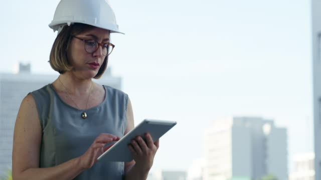 What's a civil engineer without smart apps? 4k video footage of a young businesswoman wearing a hardhat and using a digital tablet against an urban background civil engineering stock videos & royalty-free footage