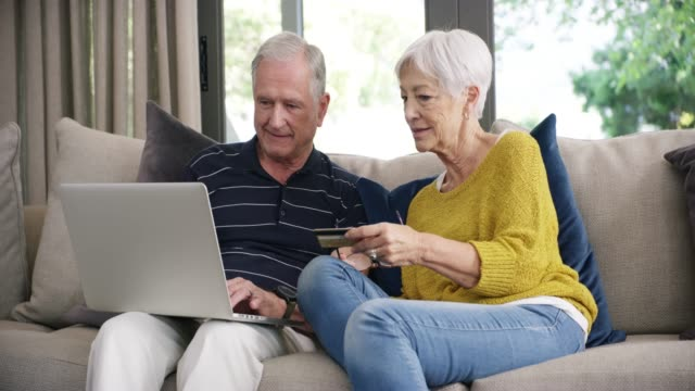 What's retirement without some indulgences? 4k video footage of a senior couple using a laptop and credit card on the sofa at home shopping online stock videos & royalty-free footage