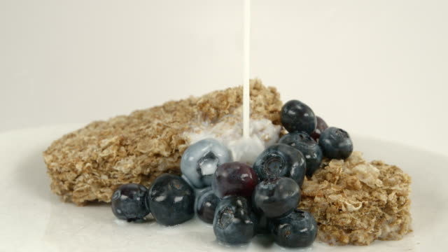 Wheat biscuit breakfast with blueberries and milk being poured in slow motion video