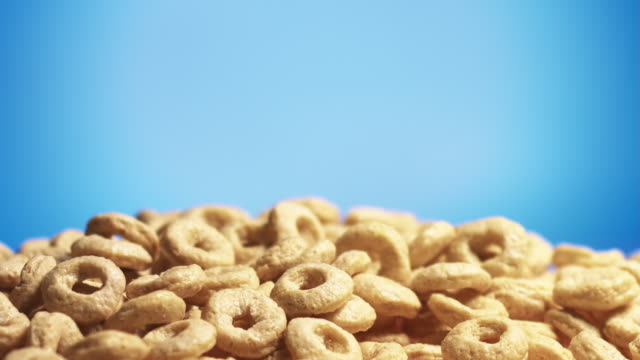 Wheat cereal rings falling on blue background video