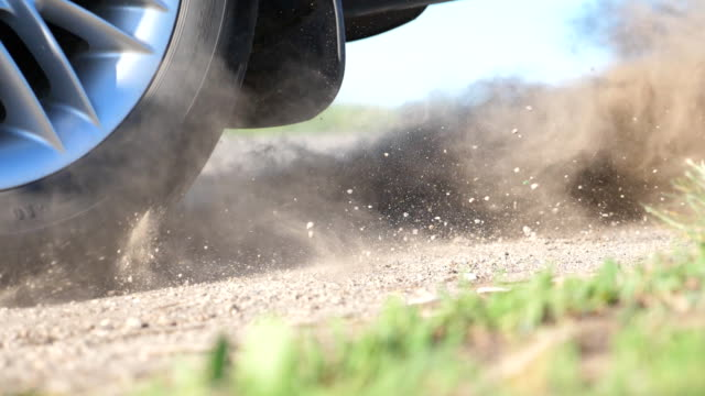 Wheel of car are slip on a dirt road during start of movement. Small stones and dirt is fly out from under the tire of a auto. Vehicle quickly beginning motion.Concept of burnout. Slow motion Close up