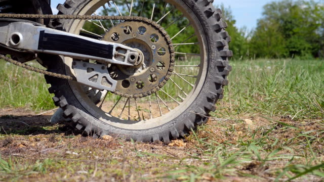 wheel of motocross bike starting to spin and kicking up ground or dirt. motorcycle starts the movement. slow motion close up side view low angle view - supercross video stock e b–roll