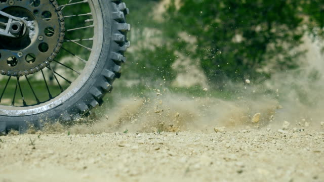wheel of motocross bike starting to spin and kicking up ground or dirt. motorcycle starts the movement. slow motion close up low angle view side view - supercross video stock e b–roll