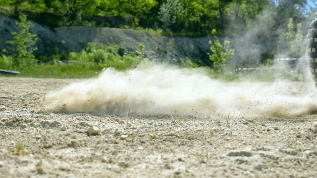 Wheel of motocross bike starting to spin and kicking up ground or dirt. Motorcycle starts the movement. Slow motion Close up Low angle view Side view