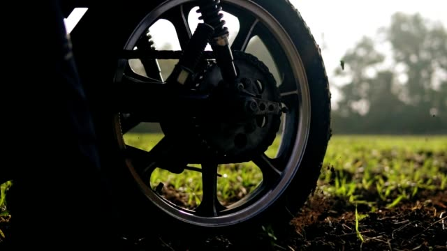 Wheel of motorcecly starting to spin and kicking up ground or dirt. Motorcycle starts the movement. Slowmotion video