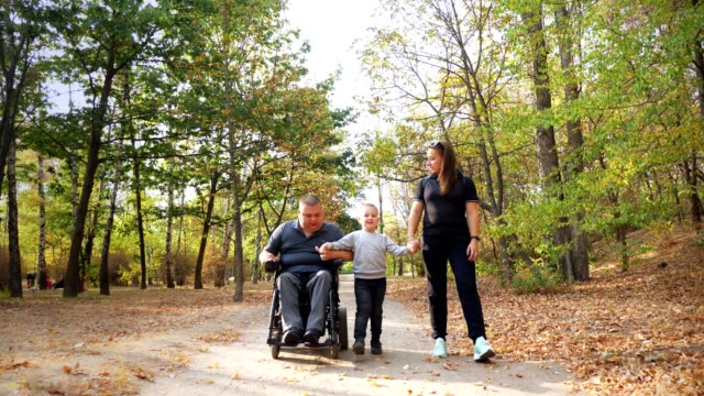 wheelchair man. Handicapped man. young disabled man in an automated wheelchair walks with his family, wife and small child, in the park, on sunny autumn day video