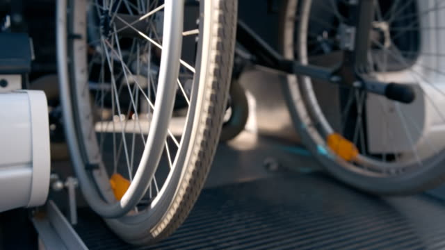 vídeos de stock e filmes b-roll de wheelchair with a disabled person is rolls out of a specially car - pessoas com deficiência