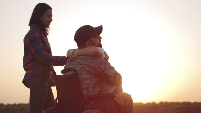 Wheelchaired soldier hugging his daughter Medium close-up of a wheelchaired soldier hugging his daughter veteran stock videos & royalty-free footage
