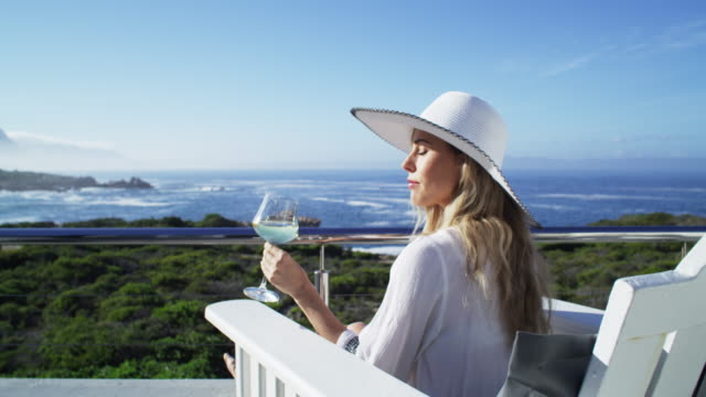 When was the last time you treated yourself? 4k video footage of a young woman having wine while relaxing on the balcony of a beach house indulgence stock videos & royalty-free footage