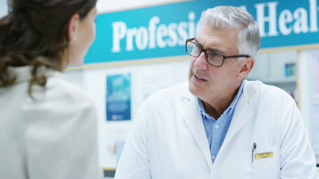 Where does it hurt? 4k video footage of a handsome senior male pharmacist helping a young woman in the pharmacy pharmacist stock videos & royalty-free footage