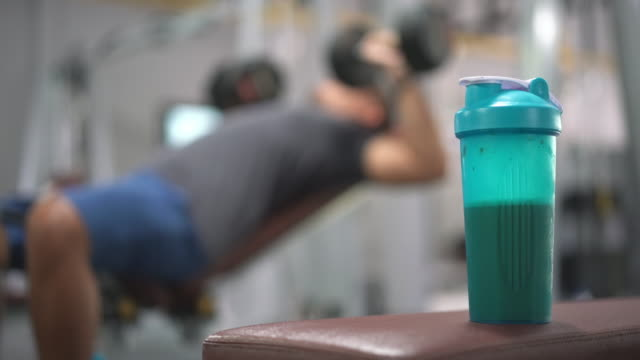 Whey Protein Shake in the gym 4K Whey Protein Shake in the gym with man working out in the background protein stock videos & royalty-free footage