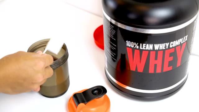 Whey protien preparing. 4K Man preparing whey protein indoor close up. protein stock videos & royalty-free footage