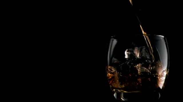 whiskey essere versato in super slow motion in un bicchiere con ghiaccio - whisky video stock e b–roll
